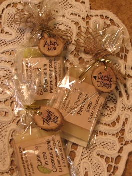 Three all natural shower favors are displayed on an old fashioned hand made doily a truly wonderful reasonably priced gift favour for any special event.  The guest bars are wrapped in cello bags and have personalized wooden gift tags with each token handmade especially for your event.  Each quality item is tied off with a burlap ribbon for an attractive rustic presentation in this inexpensive guest gift there is evidence of attention to detail from this Manitoba Artisan Canadian soap maker found in Sandy Hook, Manitoba, Canada near Gimli, Manitoba.